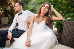 Jungvermähltencoupé, das auf einem Sofa verärgert an einander in einer Mitte eines Arguments sitzt Junges Paarproblemkonzept im F lizenzfreies stockfoto