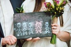 Jungvermähltenpaar hält im Handbild ihrer zukünftigen Familie, die sie von träumen Stockbilder