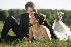 Jungvermähltenpaare, die auf dem Gebiet küssen Lizenzfreie Stockbilder