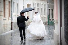 Jungvermähltenpaare im Regen lizenzfreies stockfoto