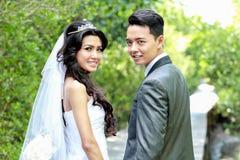 Jungvermähltenpaarhändchenhalten und zurück schauen Stockbilder