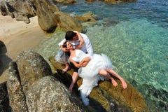 Jungvermähltenpaarportrait auf tropischen Umlagerungen Stockbild