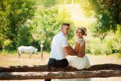 Jungvermähltenumarmung, die hinter einem Pferd sitzt lizenzfreie stockfotografie