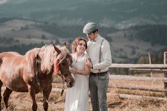 Jungverm?hlten boho Artstellung nahe Pferd auf Ranch stockfotografie