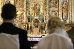 Jungvermählten an der katholischen Kirche Stockfotografie