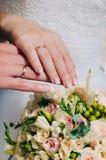 Jungvermähltenhände mit Verlobungsringen nähern sich Brautblumenstrauß Lizenzfreie Stockfotos