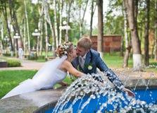 Jungvermähltenpaare, die nahe Brunnen küssen Stockfotografie