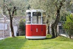 11. Juni 2017 alte rote und weiße Drahtseilbahn vor der neuen Kabelbahn Malcesine, zum von Baldo, Talstation anzubringen Lizenzfreie Stockfotografie