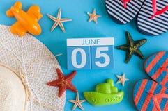 5 juni Beeld van 5 juni kalender op blauwe achtergrond met de zomerstrand, reizigersuitrusting en toebehoren Boom op gebied Royalty-vrije Stock Afbeelding
