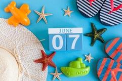 7 juni Beeld van 7 juni kalender op blauwe achtergrond met de zomerstrand, reizigersuitrusting en toebehoren Boom op gebied Royalty-vrije Stock Foto