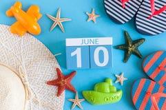 10 juni Beeld van 10 juni kalender op blauwe achtergrond met de zomerstrand, reizigersuitrusting en toebehoren Boom op gebied Royalty-vrije Stock Fotografie