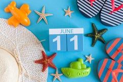 11 juni Beeld van 11 juni kalender op blauwe achtergrond met de zomerstrand, reizigersuitrusting en toebehoren Boom op gebied Stock Afbeelding