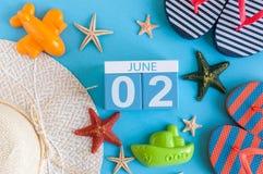 2 juni Beeld van 2 juni kalender op blauwe achtergrond met de zomerstrand, reizigersuitrusting en toebehoren zomer Stock Foto