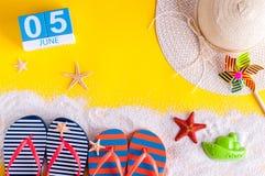 5 juni Beeld van 5 juni kalender op gele zandige achtergrond met de zomerstrand, reizigersuitrusting en toebehoren Stock Foto's