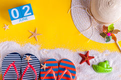 2 juni Beeld van 2 juni kalender op gele zandige achtergrond met de zomerstrand, reizigersuitrusting en toebehoren Royalty-vrije Stock Foto's
