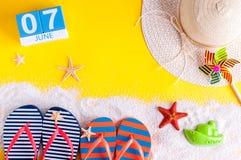7 juni Beeld van 7 juni kalender op gele zandige achtergrond met de zomerstrand, reizigersuitrusting en toebehoren Royalty-vrije Stock Fotografie