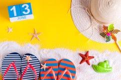 13 juni Beeld van 13 juni kalender op gele zandige achtergrond met de zomerstrand, reizigersuitrusting en toebehoren Royalty-vrije Stock Fotografie