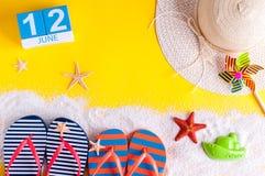 12 juni Beeld van 12 juni kalender op gele zandige achtergrond met de zomerstrand, reizigersuitrusting en toebehoren Royalty-vrije Stock Foto