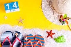 14 juni Beeld van 14 juni kalender op gele zandige achtergrond met de zomerstrand, reizigersuitrusting en toebehoren Royalty-vrije Stock Foto's