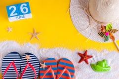 26 juni Beeld van 26 juni kalender op gele zandige achtergrond met de zomerstrand, reizigersuitrusting en toebehoren Stock Afbeeldingen