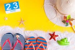 23 juni Beeld van 23 juni kalender op gele zandige achtergrond met de zomerstrand, reizigersuitrusting en toebehoren Stock Foto