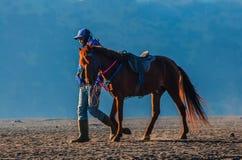 16 juni 2015 bij onderstelbromo Indonesië: de niet geïdentificeerde mens en zijn paard wachten op toerist bij bromovulkaan in Ind Stock Foto's