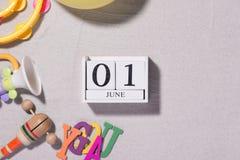 1. Juni Bild vom 1. Juni des weißen Blockkalenders mit Spielzeugwerkzeugen auf sandigem Hintergrund Lizenzfreie Stockfotografie