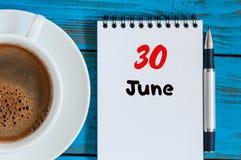 30. Juni Bild vom 30. Juni, Kalender auf blauem Hintergrund mit MorgenKaffeetasse Sommertag, Draufsicht Stockfoto