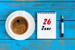 26. Juni Bild vom 26. Juni, Tagesübersicht auf blauem Hintergrund mit MorgenKaffeetasse Sommertag, Draufsicht Lizenzfreie Stockfotos