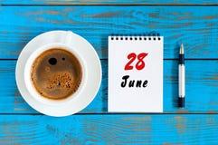 28. Juni Bild vom 28. Juni, Tagesübersicht auf blauem Hintergrund mit MorgenKaffeetasse Sommertag, Draufsicht Lizenzfreie Stockfotos