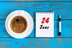 24. Juni Bild vom 24. Juni, Tagesübersicht auf blauem Hintergrund mit MorgenKaffeetasse Sommertag, Draufsicht Stockfotografie