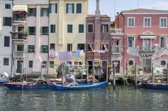 15 juni, de Zonnige dag van 2017 in Chioggia, manier om intern van het water, visserijhuisvesting in flatgebouw met vissersboten  Stock Fotografie