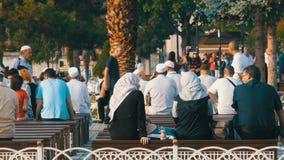 11 juni, 2019 - Istanboel, Turkije: Moslimmensen, mannen en vrouwen die in speciale robes op bank in het vierkant dichtbij zitten stock videobeelden