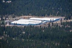 Juni 25, 2018 ogräs/CA/USA - flyg- sikt av Crystal Geyser Alpine Spring Water vid lättheten för CG som Roxane omges av skogar, arkivfoto