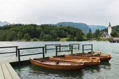 21 Juni 2018 Slovenië Vier houten boten op vastgelegd op een houten mening van de pijler Mooie berg stock afbeelding