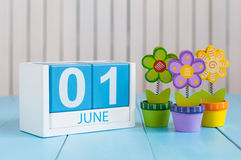 Juni 1st bild av juni 1 träfärgkalendern på blå bakgrund med blommor Första sommardag Tomt avstånd för text Arkivbild