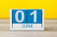 Juni 1st bild av juni 1 träfärgkalendern på gul bakgrund Första sommardag Lyckliga barns dag Arkivbilder