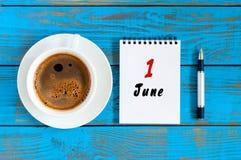 Juni 1st dag av månaden 1, daglig kalender med morgonkaffekoppen på blå träbakgrund Sommarbegrepp, överkant Arkivfoto