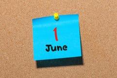 Juni 1st dag 1 av månaden, färgklistermärkekalender på anslagstavla unga vuxen människa close upp Royaltyfri Foto