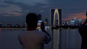 28. Juni 2018 Stadt Chinas, Suzhou, Jinji See Erwachsener Mann machen ein Foto vom schönen Sonnenuntergangstadtbild durch Smartph stock video footage