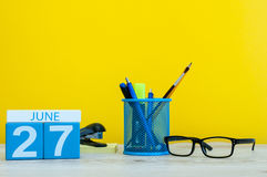 27. Juni Tag 27 des Monats, Kalender auf gelbem Hintergrund mit Büro suplies Sommerzeit bei der Arbeit international Lizenzfreie Stockfotos