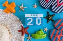 Juni 20th Bild av den juni 20 kalendern på blå bakgrund med sommarstranden, handelsresandedräkten och tillbehör field treen Royaltyfria Bilder