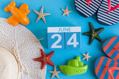 Juni 24th Bild av den juni 24 kalendern på blå bakgrund med sommarstranden, handelsresandedräkten och tillbehör field treen Arkivfoto