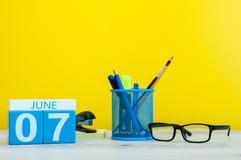 Juni 7th Dag 7 av månaden, kalender på gul bakgrund med kontorssuplies Sommartid på arbete Arkivfoton