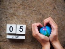 05 JUNI träkalenderkvarter, jordklot och hand på trätextur royaltyfri fotografi
