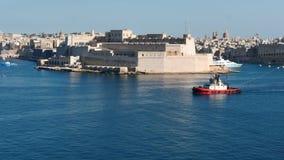 3. Juni 2016 Valletta, Malta Versuchstagboot, das Frachtschiff mit mit netter Valletta-Festungsansicht zieht stock video