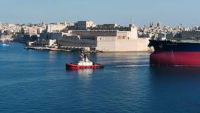 3. Juni 2016 Valletta, Malta Versuchstagboot, das Frachtschiff mit mit netter Valletta-Festungsansicht zieht stock video footage