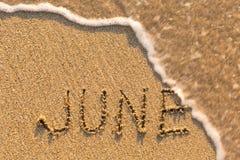 Juni - Wort gezeichnet auf den Sandstrand mit der weichen Welle Lizenzfreies Stockbild