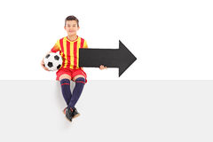 Junior athlete holding an arrow and a football royalty free stock images