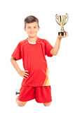 Junior athlete holding a golden trophy. Isolated on white background stock image